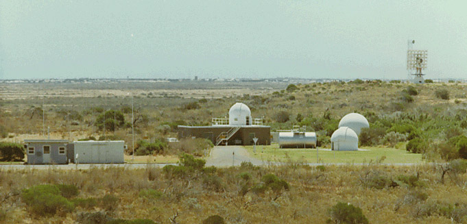 SPAN Site at the height of the Carnarvon Location Project: behind the Security Hut (on the left) are the Riometer antenna back-plane masts; centre is the SPAN building with Razdow telescope dome on the roof; to the right front is the Satellite Tracking Camera dome; just behind is the Radio Telescope radome; and near distant right, the Mobile Laser sat just to the left of the RARR VHF antenna. The Town of Carnarvon can be seen on the far distant horizon.